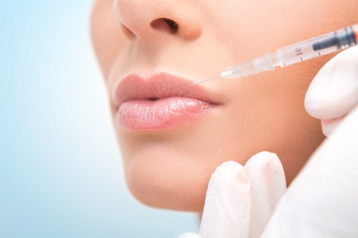 woman receiving botox injection in her lip